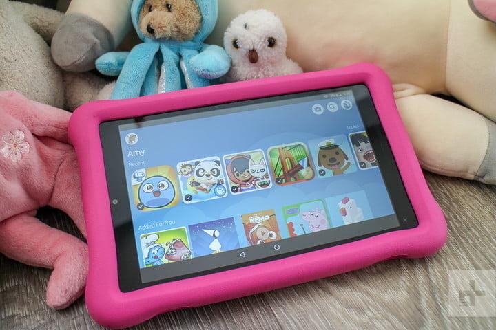 Fire HD 8 Kids Edition avec protecteur en plastique rose, sur une table en bois et quelques peluches d'un côté