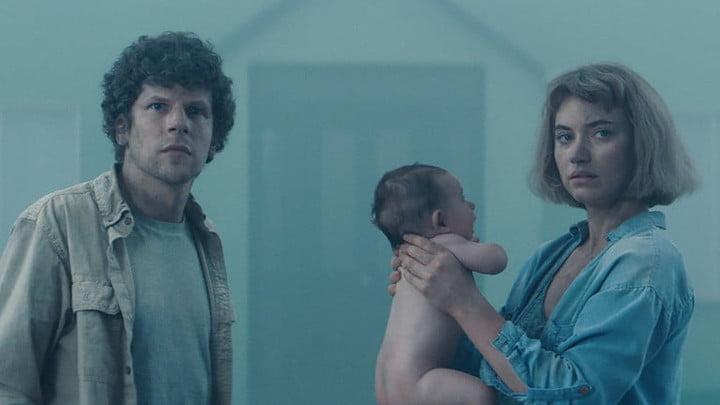 Jeune couple en vedette dans le Vivarium avec un bébé nu dans les bras.